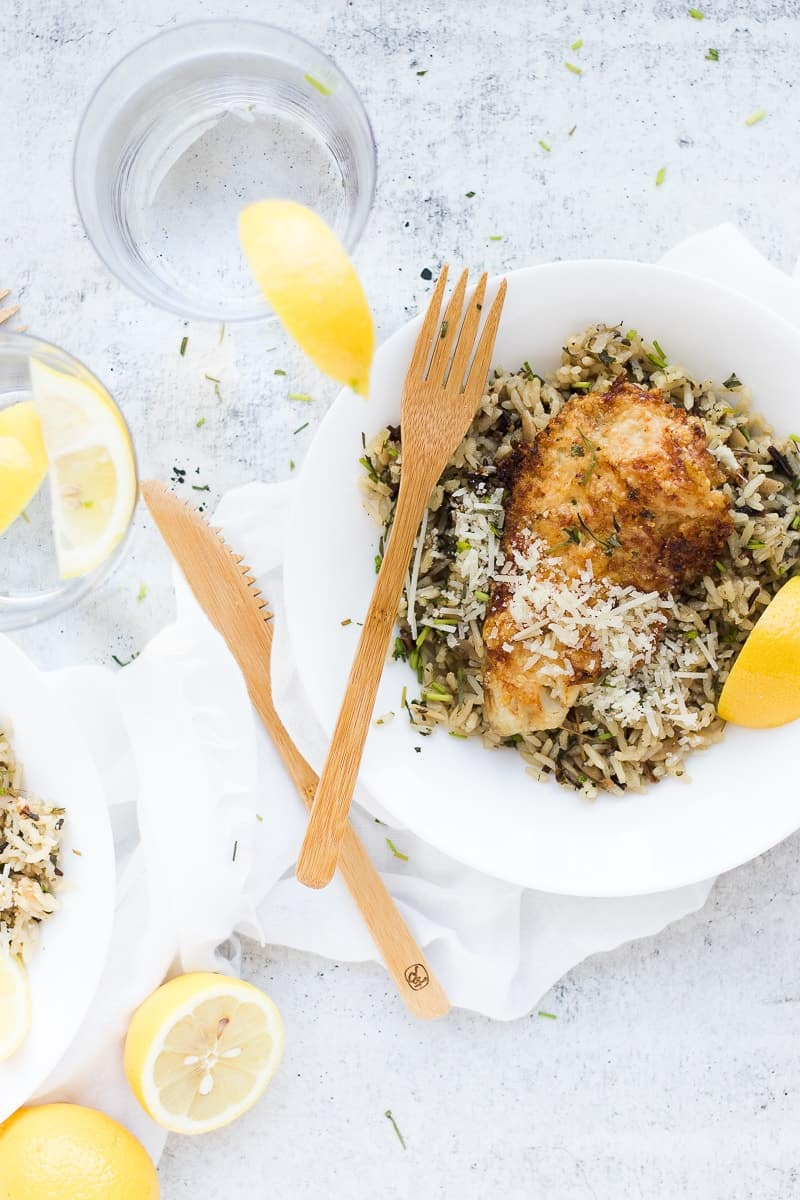 Parmesan Crusted Tilapia in bowl with rice and lemon wedges