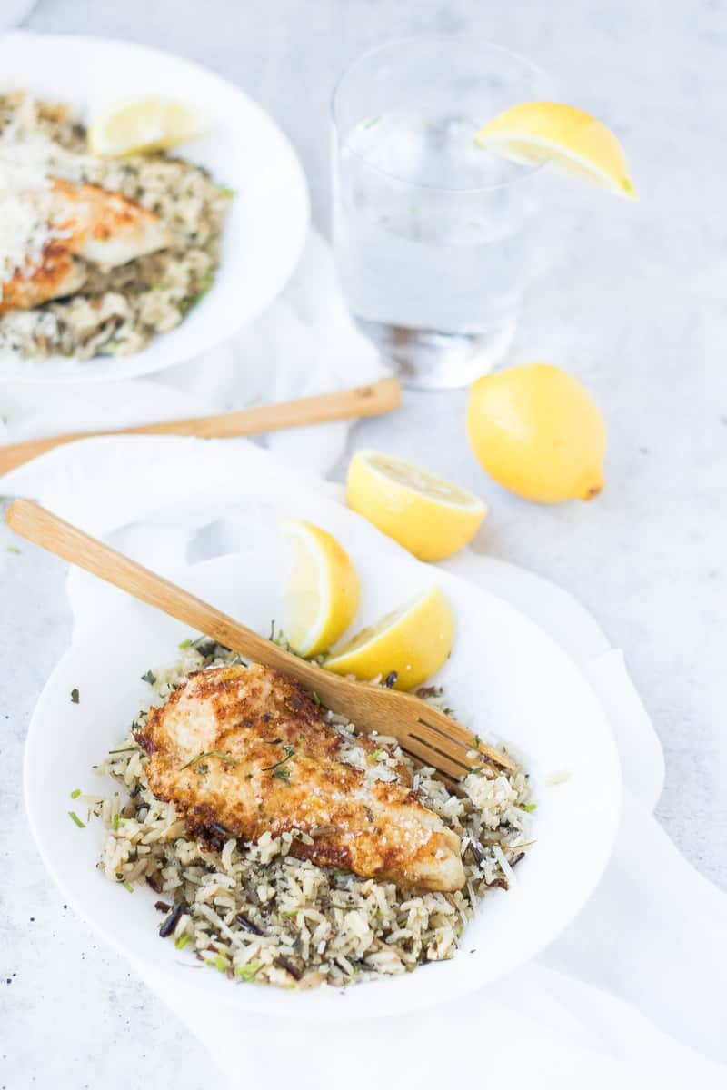 Parmesan Crusted Tilapia Recipe on rice with lemon wedges