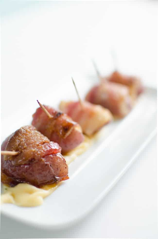 A close up of bacon Wrapped Potatoes on a white plate