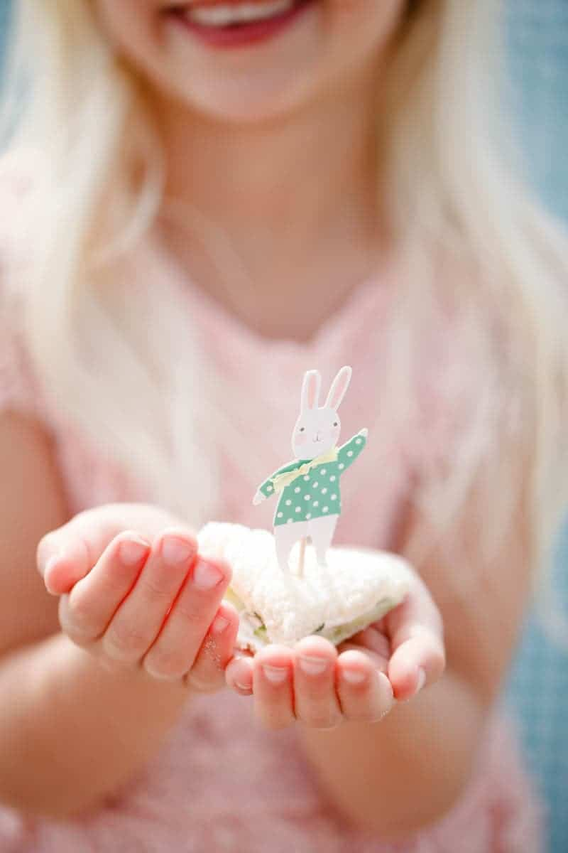 A photo of a girl holding a cucumber sandwich with an Easter bunny decoration on top