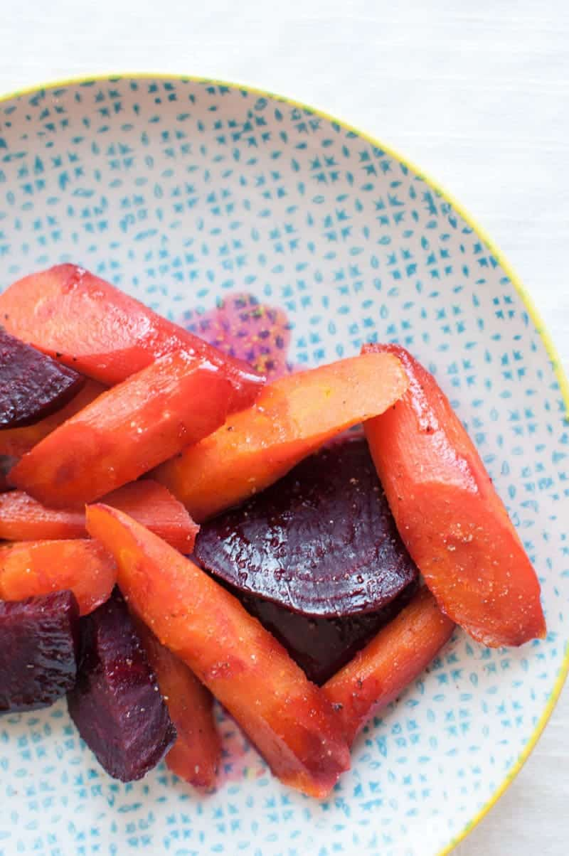 close up shot of citrus glazed carrots and beets on a plate
