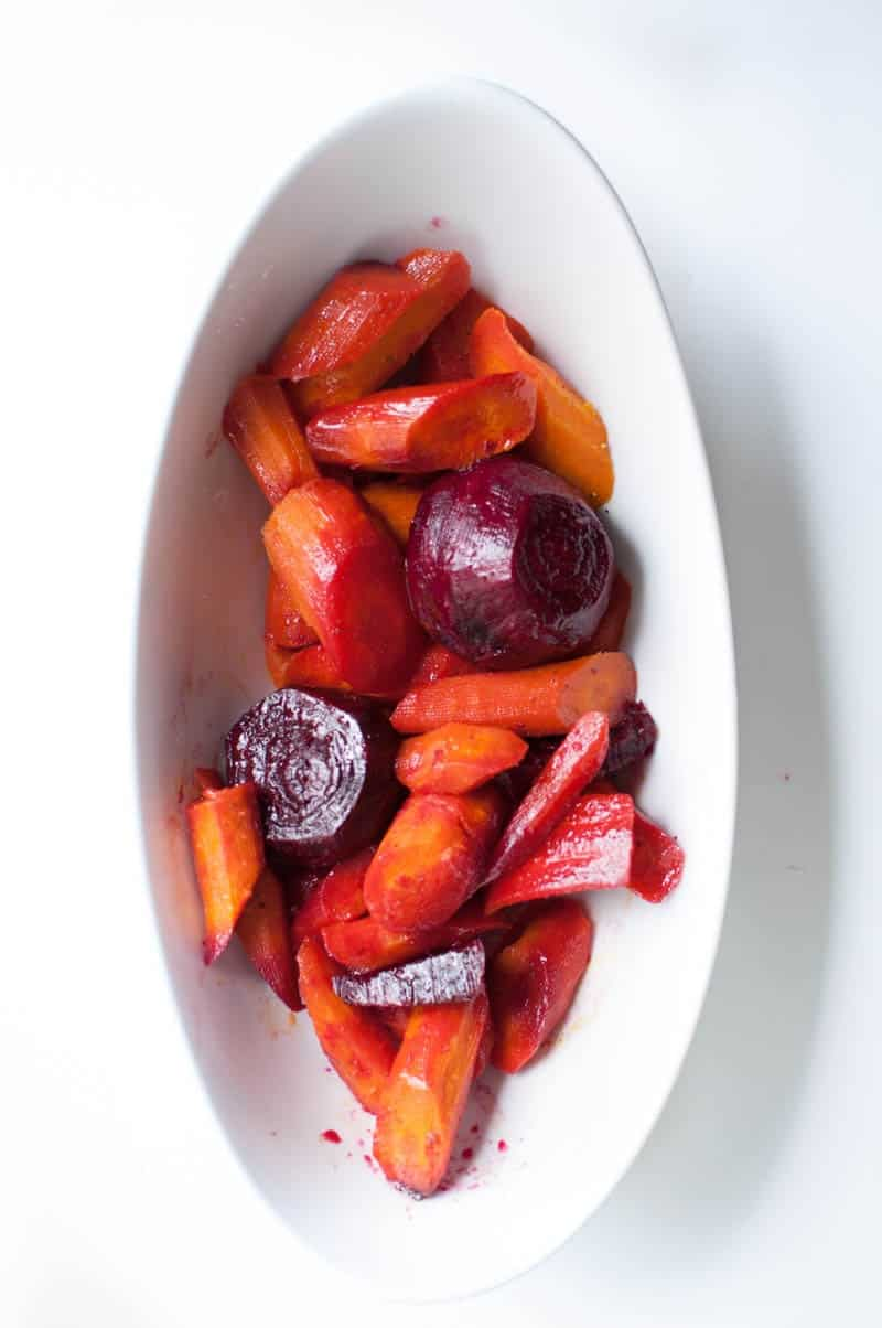 An overhead shot of glazed beets and carrots in oval dish