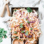 Homemade coleslaw recipe in a metal cake pan, dressing to the side.