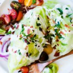 wedge salad with blue cheese dressing, bacon, herbs and cherry tomatoes