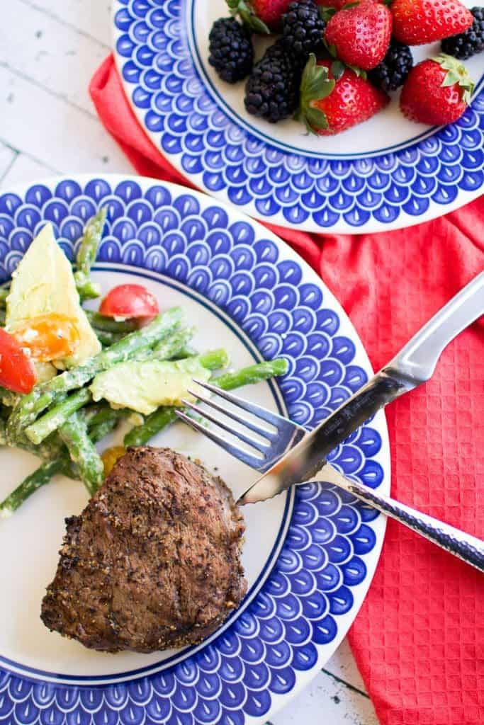 A steak on a plate next to veggies