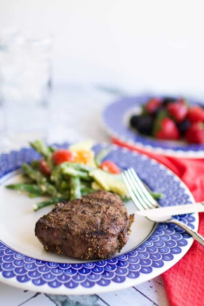 A grilled steak on a blue plate with veggies