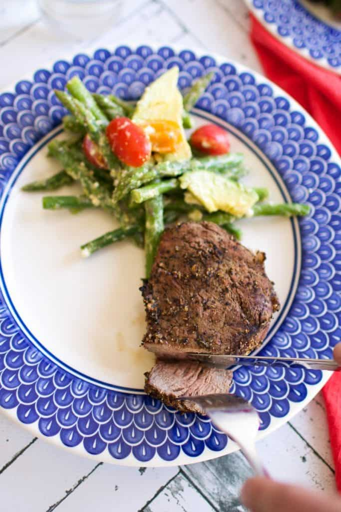 Someone cutting a steak on a blue plate with a side of veggies