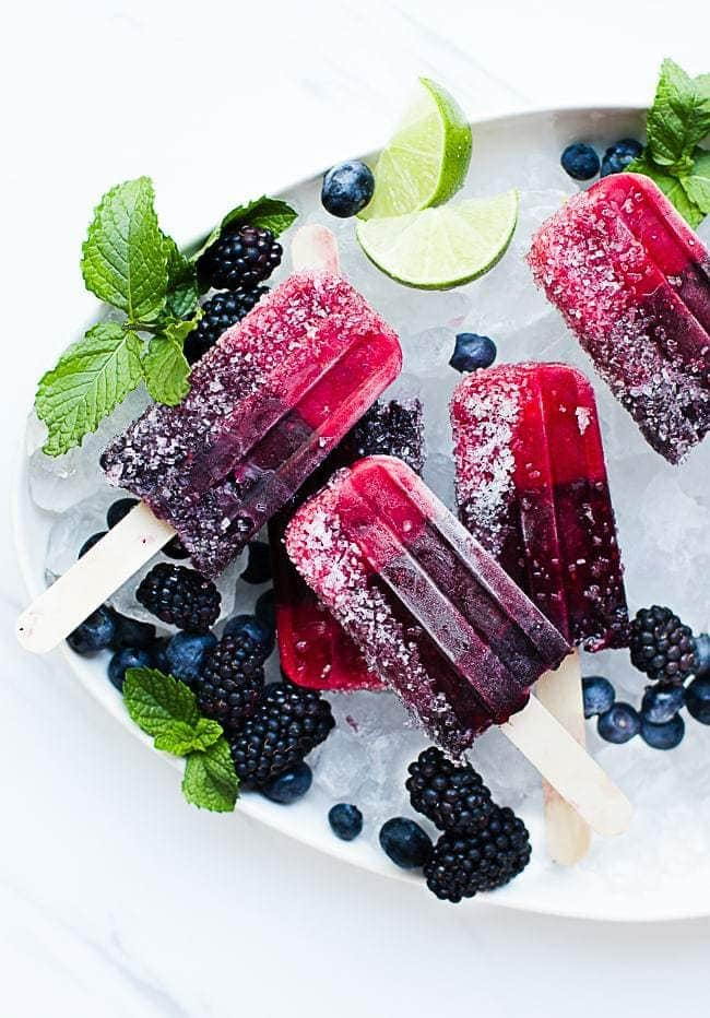 An overhead shot of triple berry popsicles on a tray of ice with berries scattered around