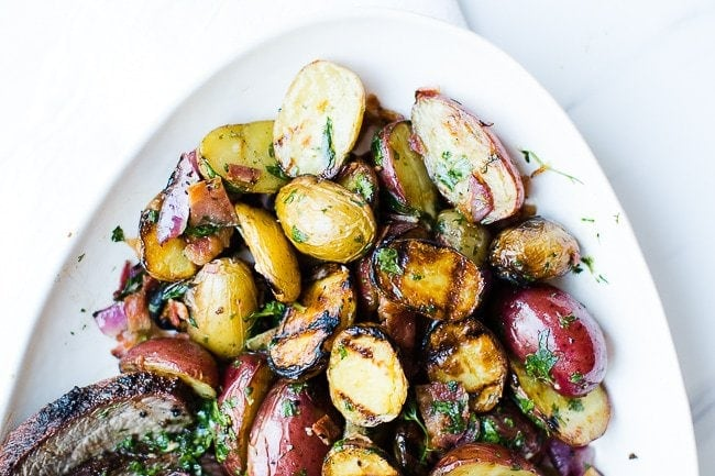 A close up of grilled potato salad on a white dish