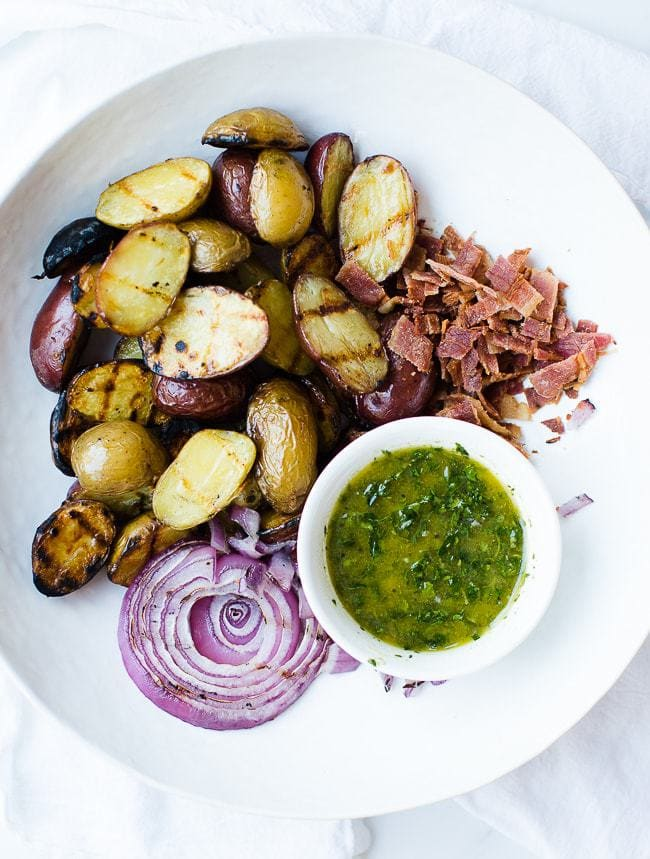 grilled potatoes, chopped bacon, grilled purple onion and dressing in bowl