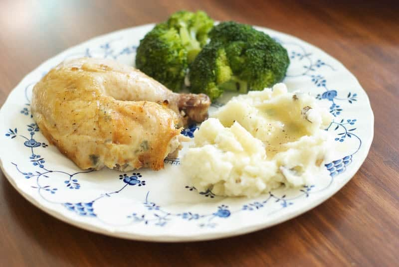 roasted chicken on plate with mashed potatoes and steamed broccoli