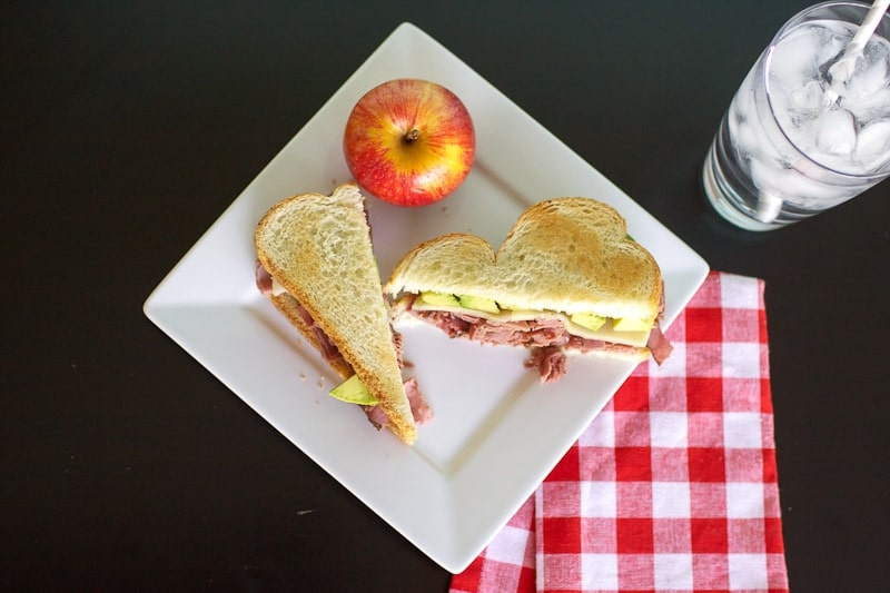 cut pastrami sandwich on plate with apple