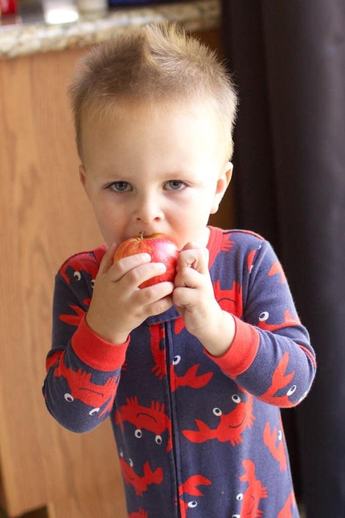 toddler getting bite of apple