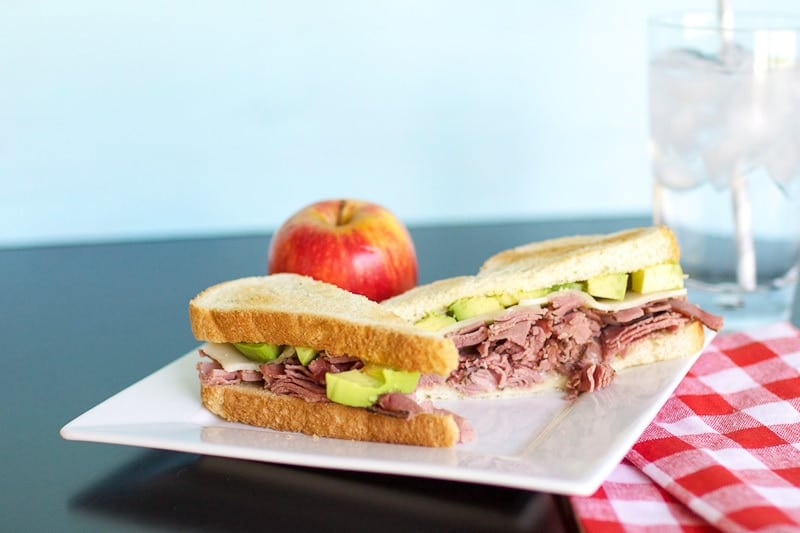 Pastrami sandwich on plate with apple