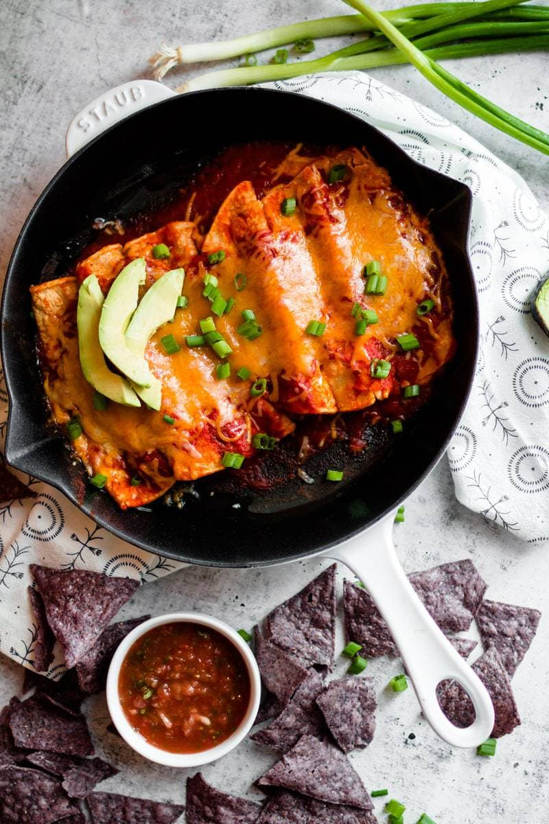 Enchiladas with homemade enchilada sauce in a cast iron skillet with tortilla chips