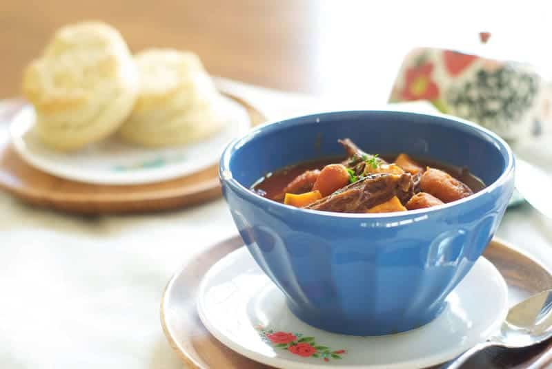 Indian Spiced Fall Roast Beef Stew in blue bowl with fresh biscuits in the background