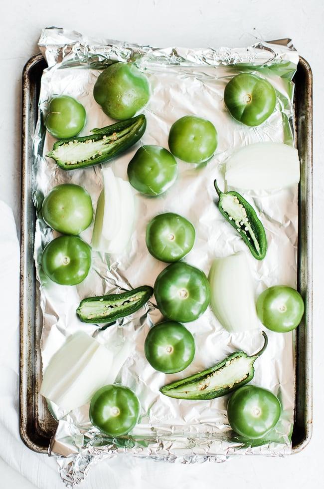 tomatillos, onion, and jalapeños on sheet pan
