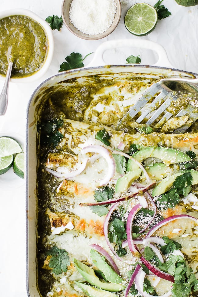 messy, cheesy green green enchiladas in a pan