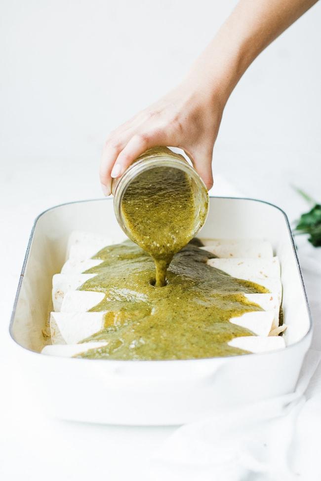 Jar pouring green enchilada sauce over enchiladas