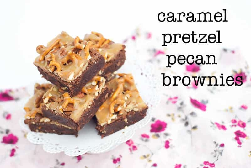 A stack of Caramel Pretzel Pecan Brownies on a cake stand