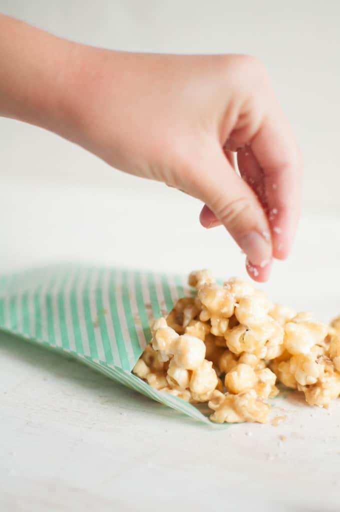 A hand sprinkling salt on Soft Caramel Popcorn