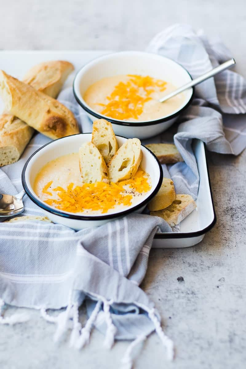 Creamy Cheddar Cauliflower Soup topped with cheddar, baguette slices inside bowl of soup