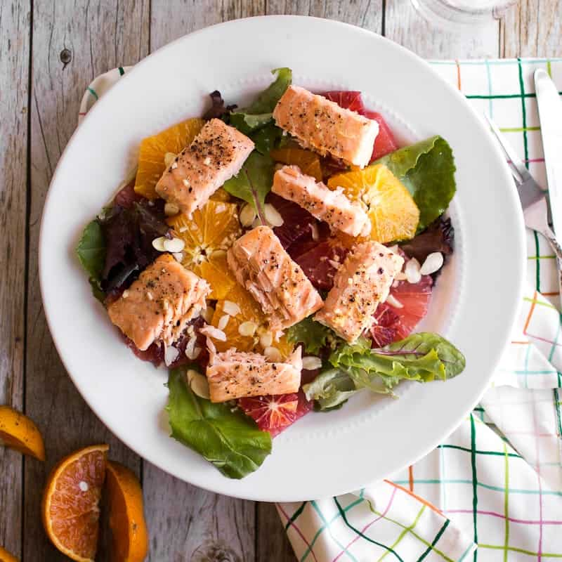 Citrus and Salmon Salad, overhead shot. plate on colored grid cloth, cut oranges to the side