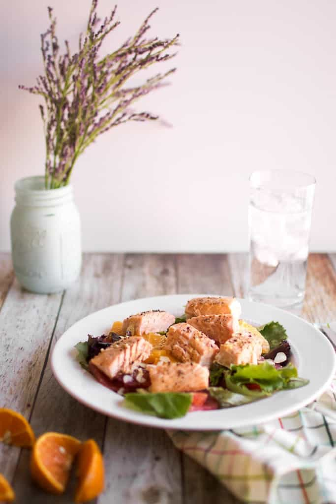 Citrus and Salmon Salad on a white plate, cut oranges on the side, vase of lavender in the background