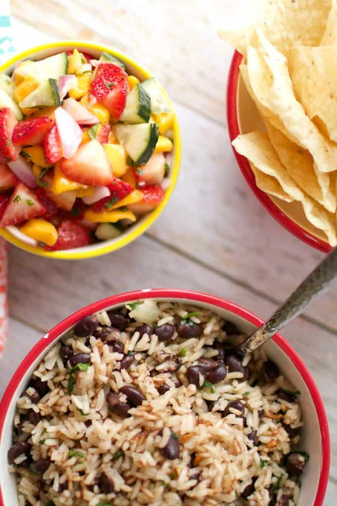 Caribbean Rice and Beans in a red bowl with strawberry mango pico at the side