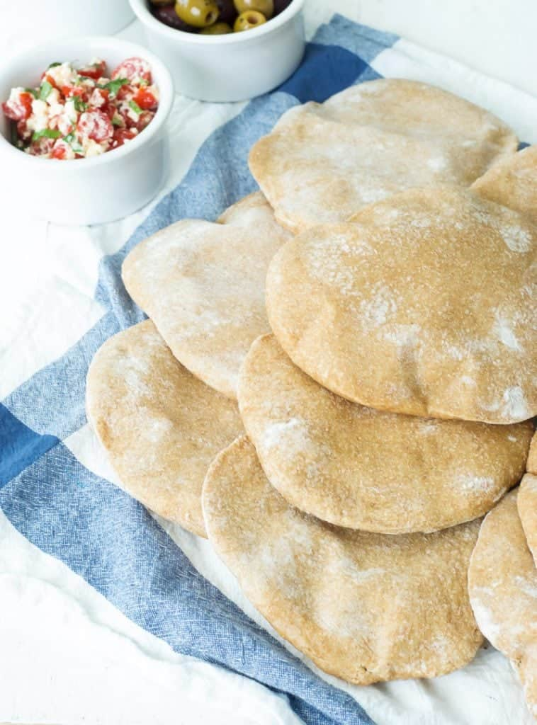 Whole Wheat Pita Breads piled on top of each other on a dish cloth with pita fillings in the background