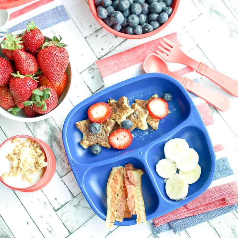 A blue tray filled with easy french toast, berries, banana and bacon for a kid's breakfast