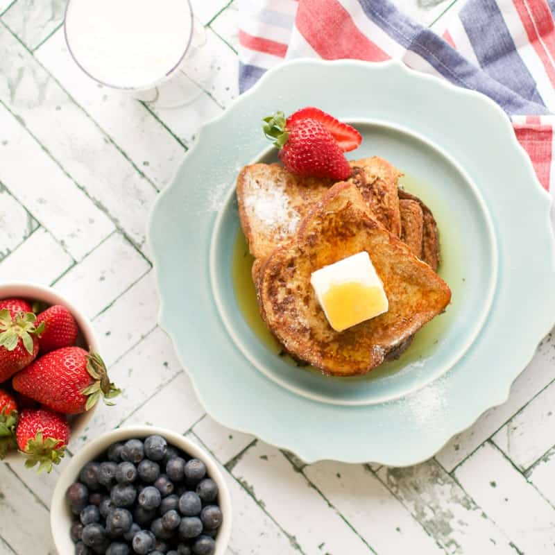 A close up of easy french toast on a blue plate topped with butter, syrup and berries