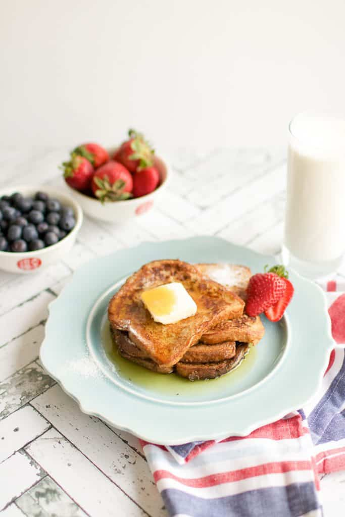 A side shot of easy French Toast on a blue plate with a glass of milk in the background and berries