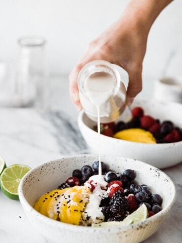 coconut syrup pouring over bowl of fruit and quinoa