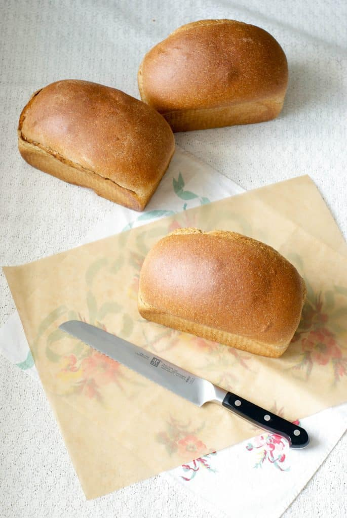 3 loaves of 100% Whole Wheat Bread on a white surface with a bread knife