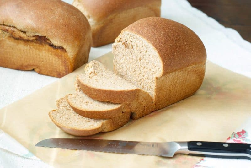 100% Whole Wheat Bread loaf cut into slices with a bread knife at the side