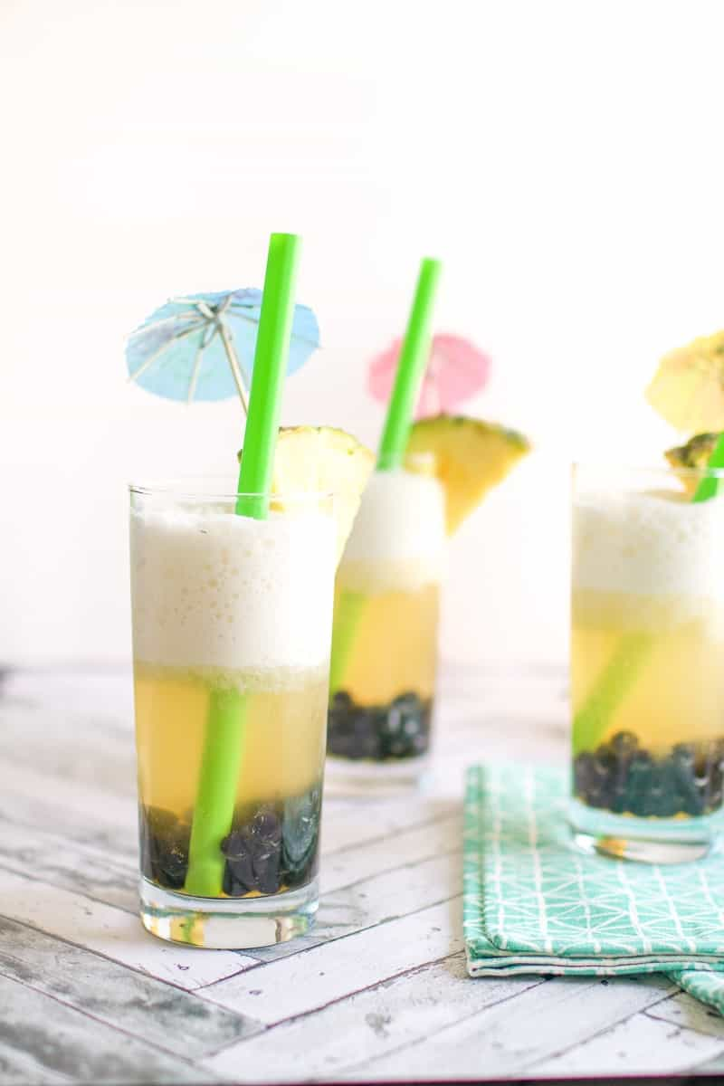 A close up of coconut pineapple iced tea with boba pearls