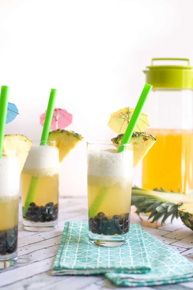 A close up of coconut pineapple boba tea in glasses with green straws