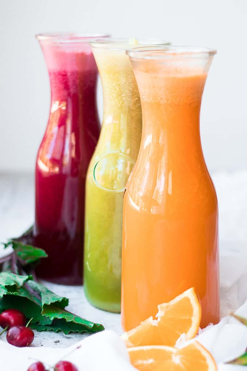red, green, and orange juices in glass juice decanters