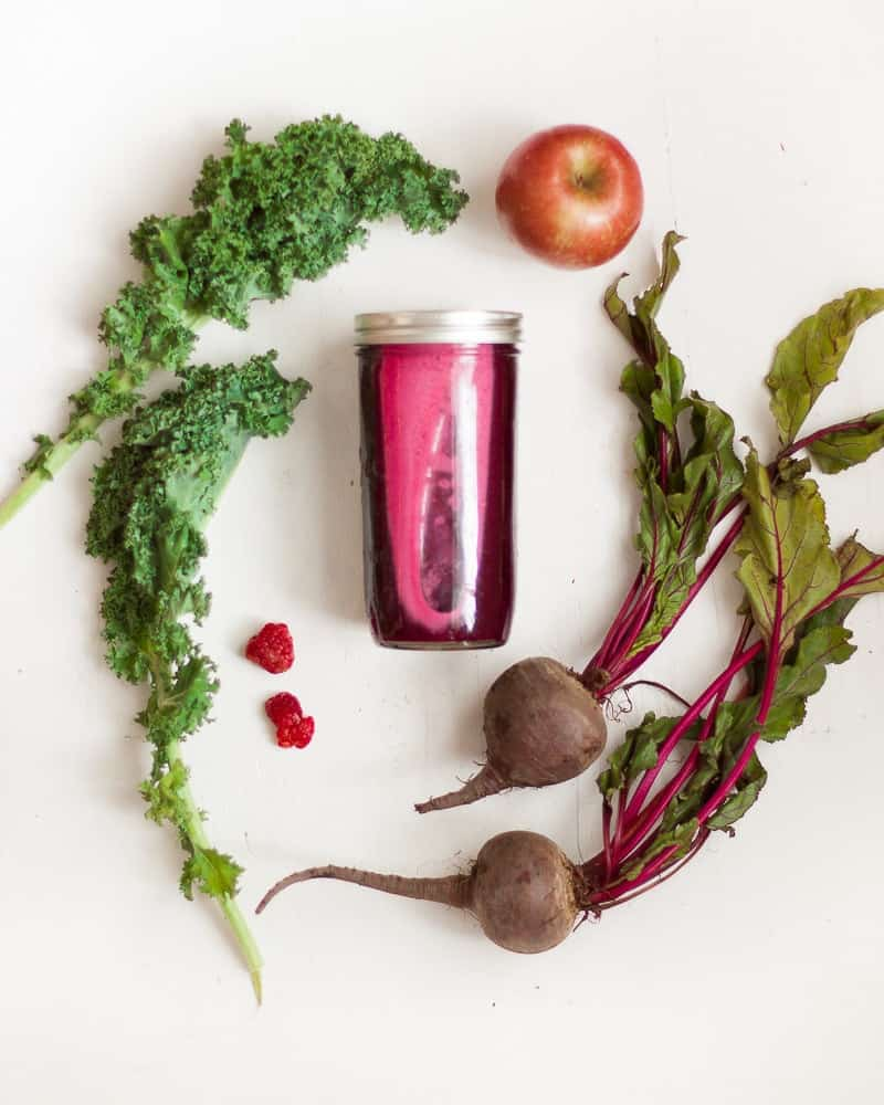 mason jar filled with red juice surrounded by fresh ingredients used to make juice