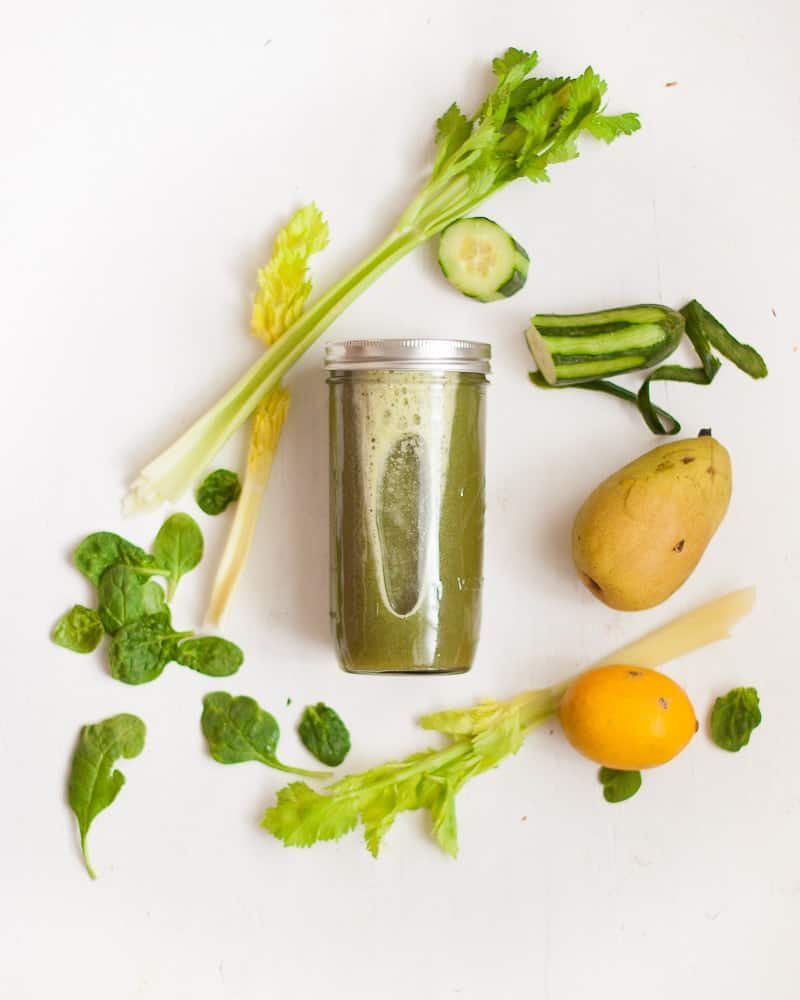 green juice in mason jar surrounded by green juice ingredients