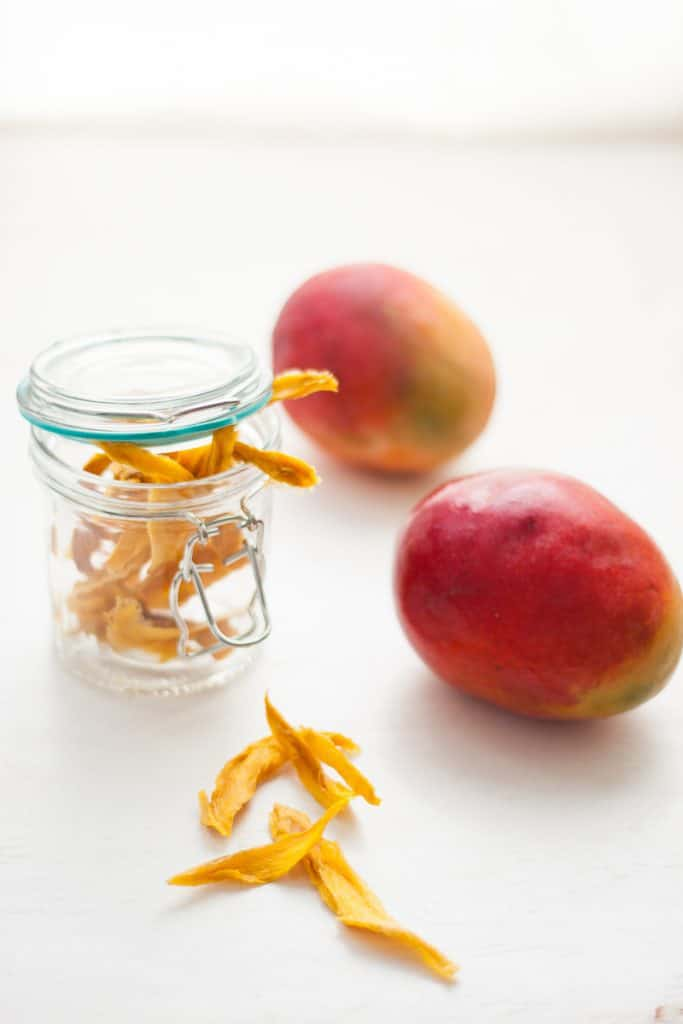 Dried mango in a glass jar with 2 mangoes at the side