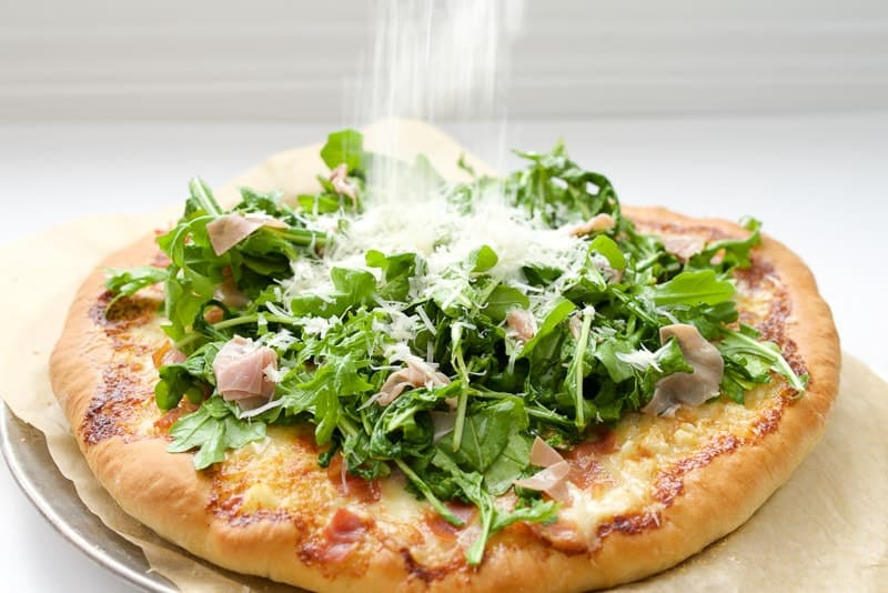 Prosciutto and Arugula Alfredo Pizza with parmesan getting sprinkled on top