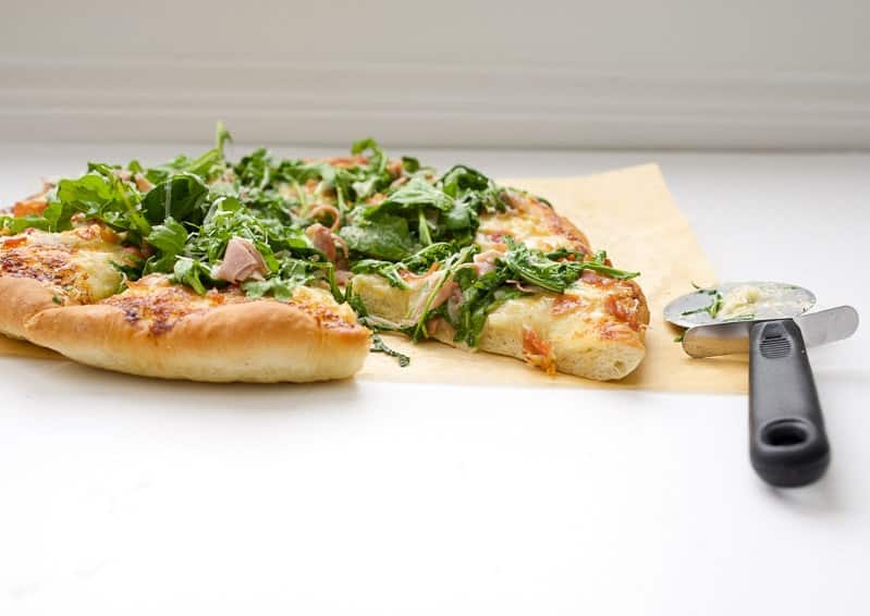 A side shot of a prosciutto and Arugula Alfredo Pizza with a pizza wheel at the side