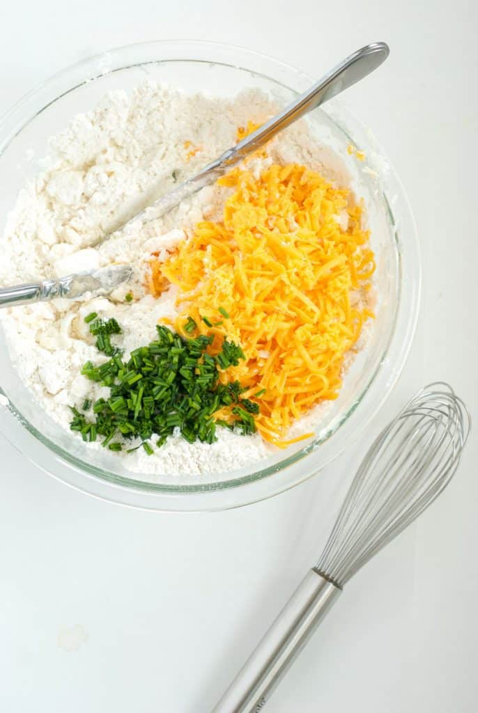 An overhead shot of ingredients in a bowl to make cheese biscuits
