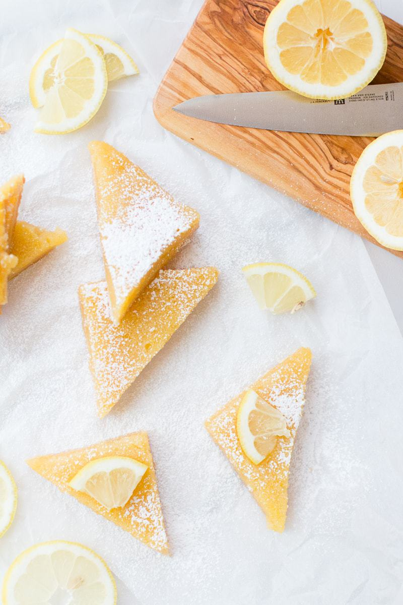 lemon bars with fresh lemons on a cutting board