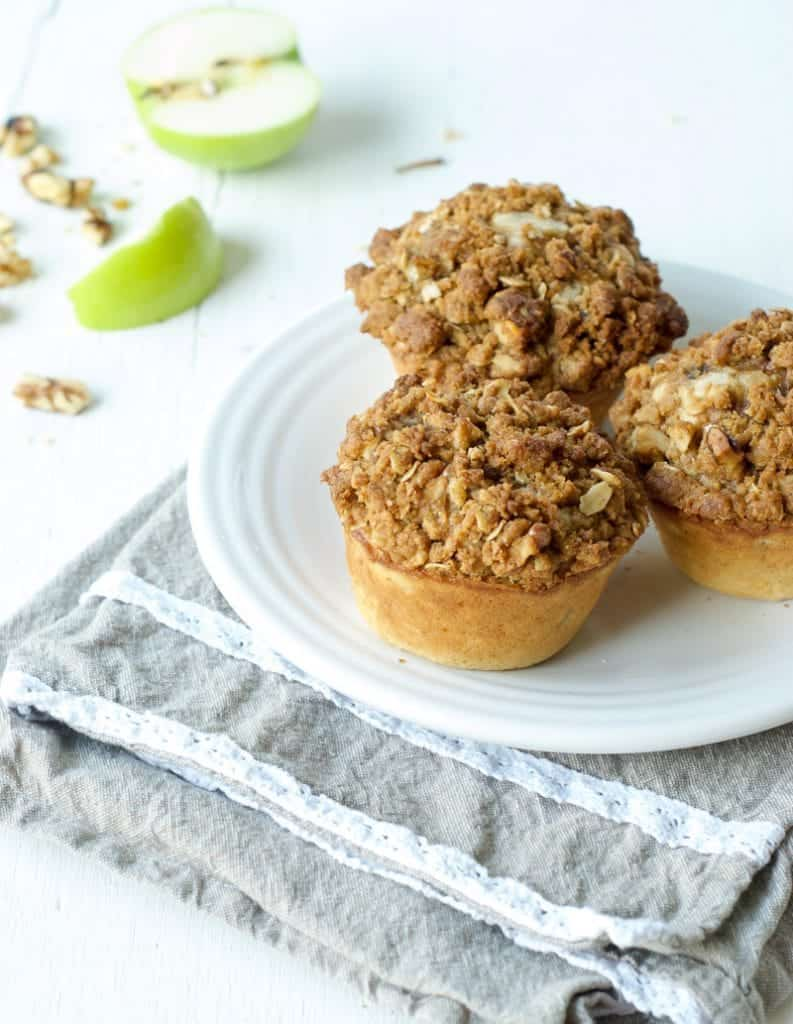 Cardamom apple muffins on a white plate with apple in the background