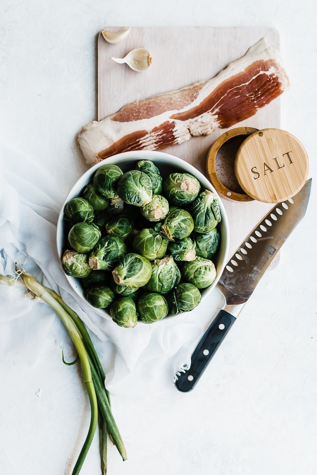 Brussel sprouts with bacon and garlic ingredients on a white washed cutting board.