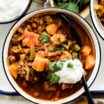 one bowl of chili with sour cream and cilantro