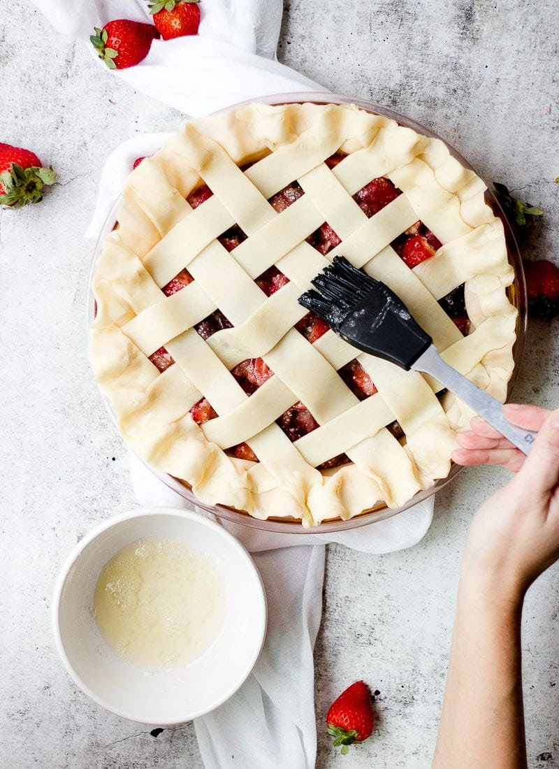 Tart Strawberry Rhubarb Pie being brushed with melted butter